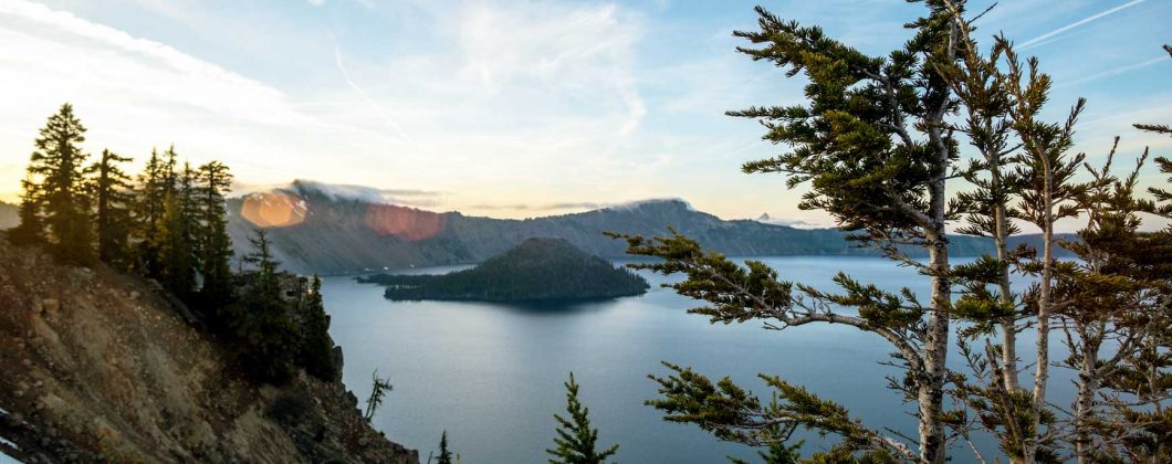 Outdoor panoramic shot of crater lake at sunset