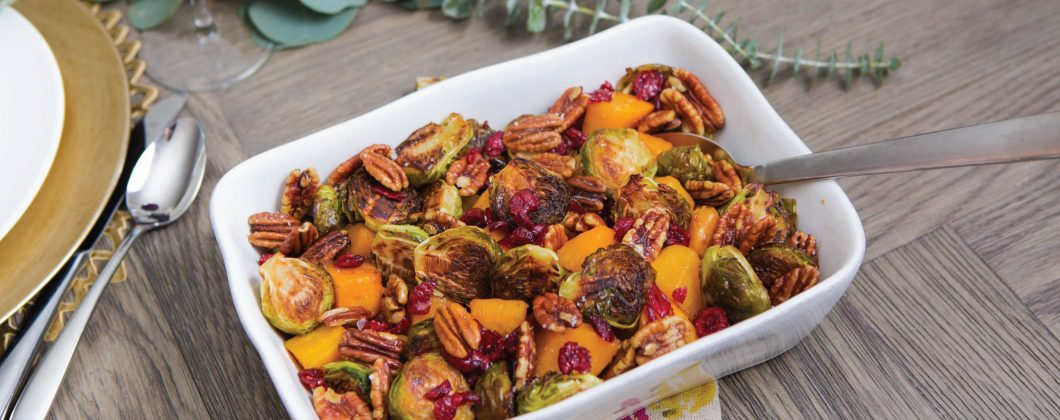 A casserole dish of roasted butternut squash and brusselsprouts
