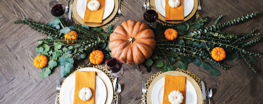 Aerial table shot - pumpkin, fall leafy decorations, four plate settings