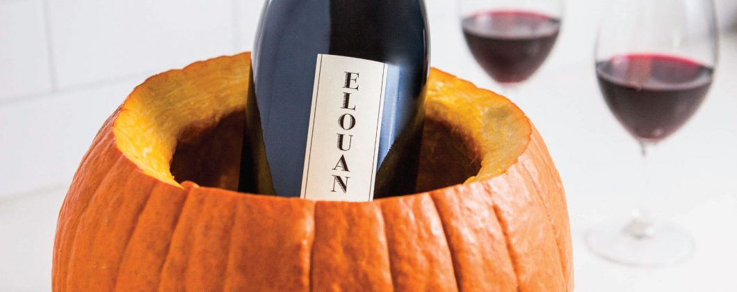 Elouan pinot noir inside a carved pumpkin next to two glasses of Elouan pinot noir